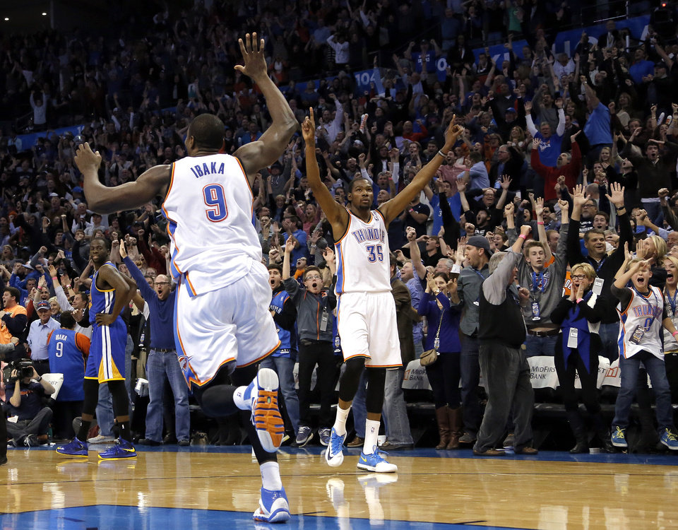 Photo - Oklahoma City's Serge Ibaka (9) and Kevin Durant (35) celebrate Russell Westbrook's game-winning three pointer in the overtime of the NBA game between the Oklahoma City Thunder and the Golden State Warriors at the Chesapeake Energy Arena, Friday, Nov. 29, 2013. Photo by Sarah Phipps, The Oklahoman