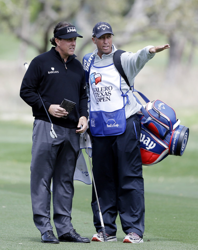 Photo - Phil Mickelson, left, gets direction from his caddie as he takes part in a pro-am at the Valero Texas Open, Wednesday, March 26, 2014, in San Antonio. Mickelson is straying from his usual schedule and playing in the Valero Texas Open for the first time in 22 years. (AP Photo/Eric Gay)