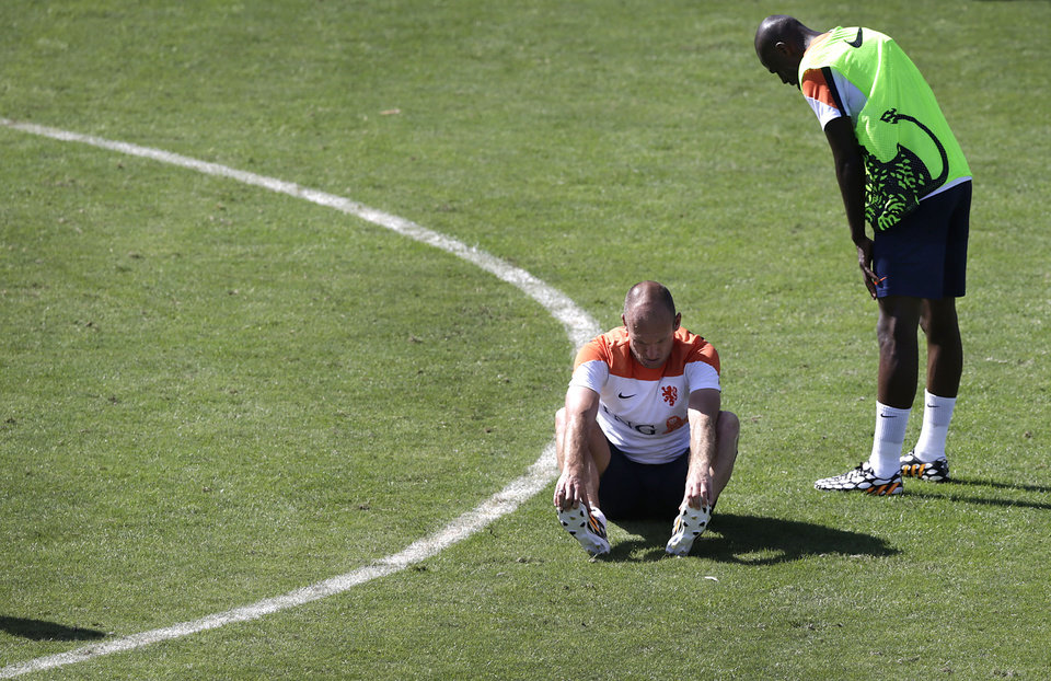 Photo - Arjen Robben, left, sits on the ground after being tackled by Bruno Martins Indi, right, both from the Netherlands soccer team during a training session in Rio de Janeiro, Brazil, Sunday June 8, 2014. Arjen Robben has reacted angrily to a tough challenge from Netherlands teammate Bruno Martins Indi during a World Cup training session at their base in Rio. The Netherlands play in group B of the 2014 soccer World Cup. (AP Photo/Wong Maye-E)