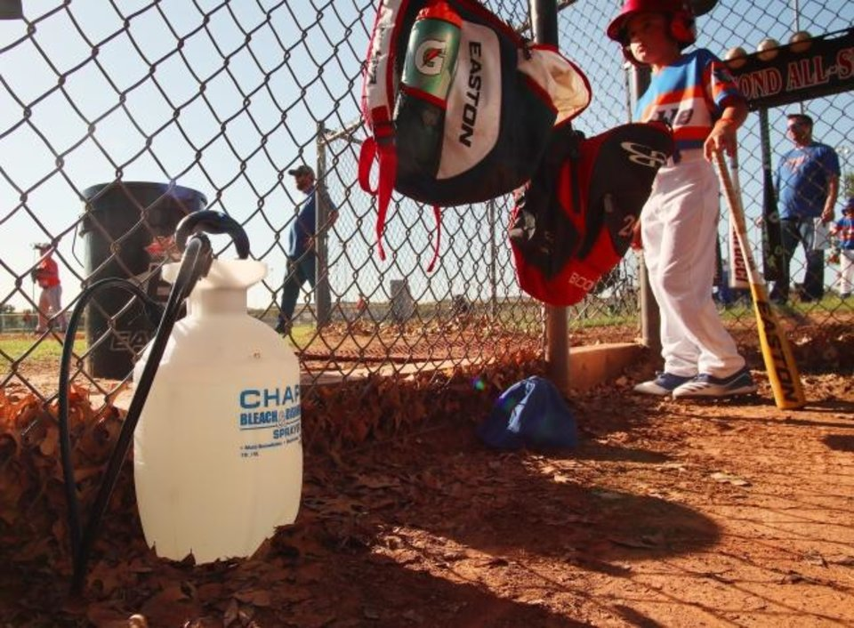 Photo -  As youth sports reopen after the coronavirus shutdown, safety measures are being taken. Bleach spray bottles are used in dugouts between each game in the Edmond All Sports league. Spectators are limited and asked to maintain social distance. Face coverings are not required. [DOUG HOKE/THE OKLAHOMAN]