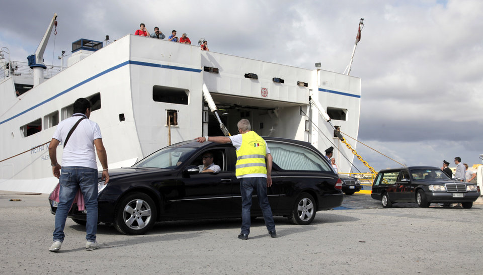 Photo - Mortuary vehicles disembark from a ferry at the port of Lampedusa, Italy, Friday, Oct. 4, 2013. A ship carrying African migrants towards Italy capsized off the Sicilian island of Lampedusa Thursday, spilling hundreds of passengers into the sea, officials said. Authorities resumed Friday their search for bodies in the migrant shipwreck, in which officials say just 155 people survived of the 450 to 500 believed to have been on board. It was one of the deadliest accidents in the perilous crossing thousands make each year, seeking a new life in the prosperous European Union. (AP Photo/Francesco Malavolta)