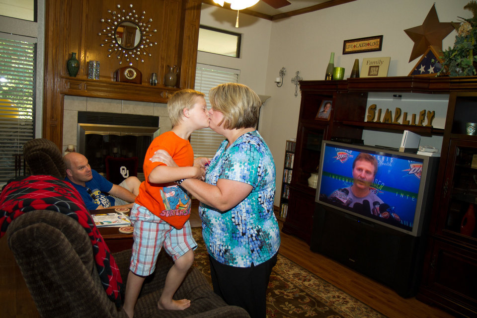 Photo - Lori Wathen gets a kiss from her 9-year-old son, Reis, as they watch the start of the Thunder game at their home in Norman. Photo by Steven Maupin, for The Oklahoman.  Steven Maupin
