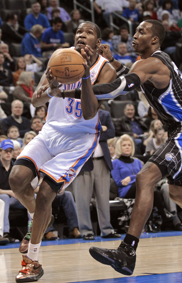 Orlando Magic's Dwight Howard (12) fouls Oklahoma City Thunder's Kevin Durant (35) in the second half as the Oklahoma City Thunder defeat the Orlando Magic 97-89 in NBA basketball at the Chesapeake Energy Arena on Sunday, Dec. 25, 2011, in Oklahoma City, Okla.  Photo by Steve Sisney, The Oklahoman