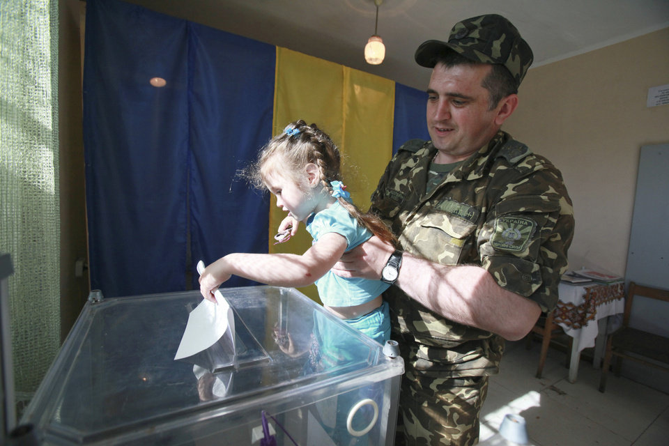 Photo - A Ukrainian soldier with his daughter, casts his ballot during voting in the presidential election at a polling station in the village of Kovyri in the Lviv region of western Ukraine, Sunday, May 25, 2014. Ukraine's critical presidential election got underway Sunday under the wary scrutiny of a world eager for stability in a country rocked by a deadly uprising in the east. (AP Photo/ Petro Zadorozhnyy)
