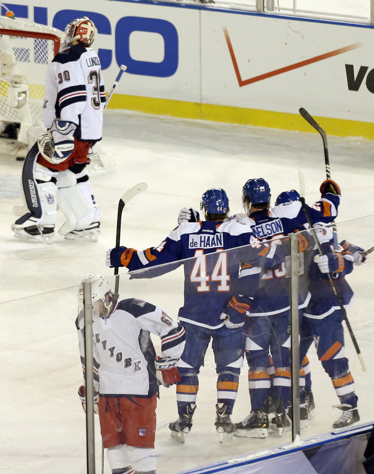 Photo - New York Rangers goalie Henrik Lundqvist (30) and teammate Benoit Pouliot (67) react as the New York Islanders celebrate a goal by Brock Nelson during the second period of an outdoor NHL hockey game  Wednesday, Jan. 29, 2014, at Yankee Stadium in New York. (AP Photo/Frank Franklin II)