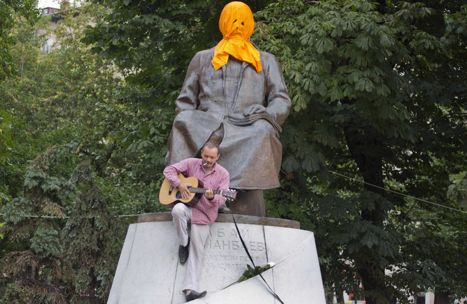 Photo -   A man plays a guitar while resting on the base of a monument to Kazakh poet Abai Kunanbaev in Moscow on Friday, Aug. 17, 2012, with the face covered with a mask to resemble feminist punk group Pussy Riot members. The three women in the band Pussy Riot have been in jail for more than five months because of a prank in Moscow's main cathedral against Russia's Vladimir Putin, and they face a maximum seven years in jail, as they await a verdict Friday on charges of hooliganism motivated by religious hatred. (AP Photo/Yevgeny Feldman, Novaya Gazeta)