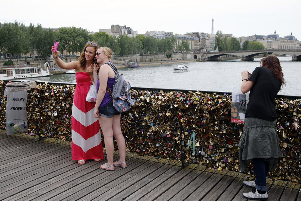 Photo - Tourists take selfies with their phone on the Pont des Arts bridge in Paris, Monday, June 9, 2014. The thousands of locks that cling like barnacles to the Pont des Arts in Paris have become a symbol of danger, rather than love, after a chunk of fencing fell off under their weight. The fencing tumbled late Sunday on the pedestrian bridge, which crosses the Seine. (AP Photo/Francois Mori)