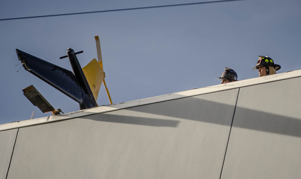 Photo - Firefighters study the helicopter  tail hanging over the edge of the UNM Hospital  Wednesday afternoon April 9, 2014, after it crashed as it took off from the roof of the building.     (AP Photo/The Albuquerque Journal, Roberto E. Rosales)  THE SANTA FE NEW MEXICAN OUT
