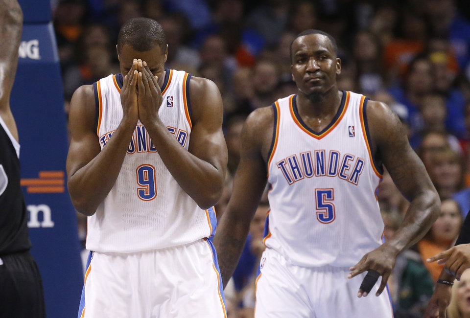 Photo - Oklahoma City Thunder forward Serge Ibaka (9) reacts after being called for offensive interference in the second quarter of an NBA basketball game against the Sacramento Kings in Oklahoma City, Sunday, Jan. 19, 2014. Thunder center Kendrick Perkins (5) looks on. (AP Photo/Sue Ogrocki)