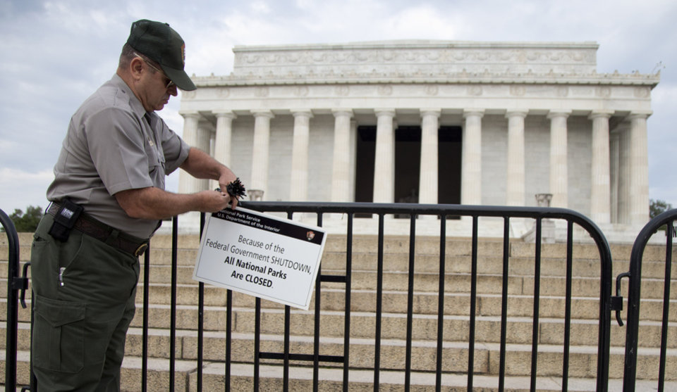 Photo - A National Park Service employee posts a sign on a barricade to close access to the Lincoln Memorial in Washington, Tuesday, Oct. 1, 2013. Congress plunged the nation into a partial government shutdown Tuesday as a long-running dispute over President Barack Obama's health care law stalled a temporary funding bill, forcing about 800, 000 federal workers off the job and suspending most non-essential federal programs and services. (AP Photo/Carolyn Kaster)