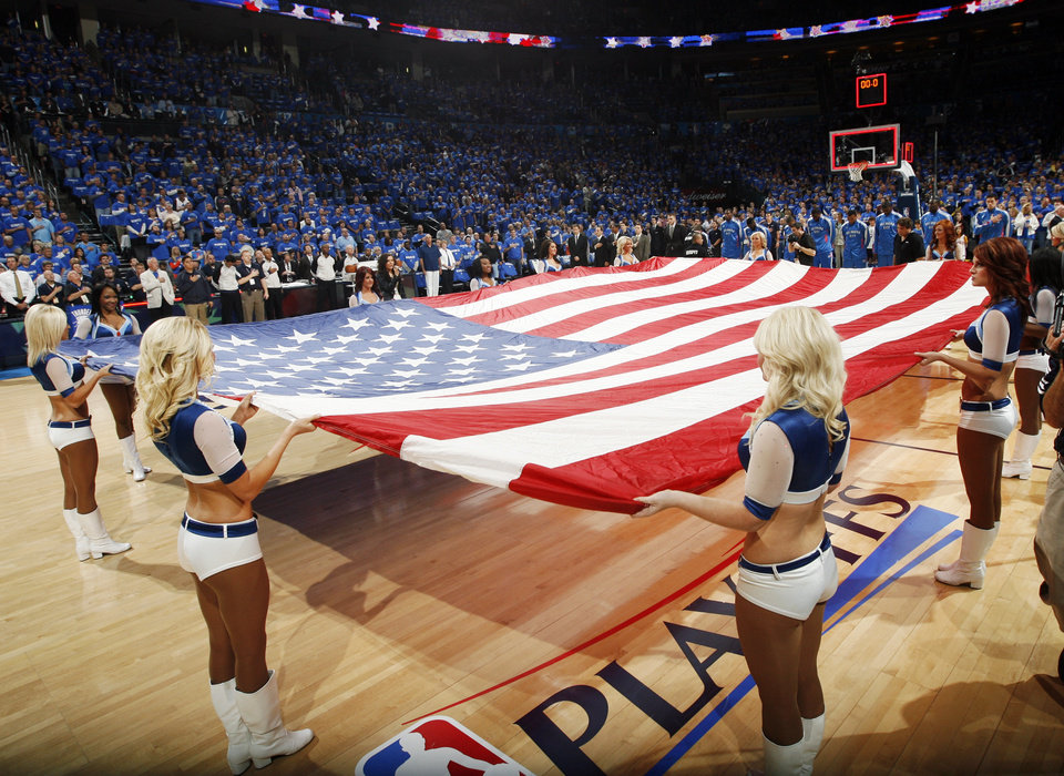 Photo - The Thunder Girls hold an American flag during the singing of the national anthem before game one of the Western Conference semifinals between the Memphis Grizzlies and the Oklahoma City Thunder in the NBA basketball playoffs at Oklahoma City Arena in Oklahoma City, Sunday, May 1, 2011. Photo by Nate Billings, The Oklahoman