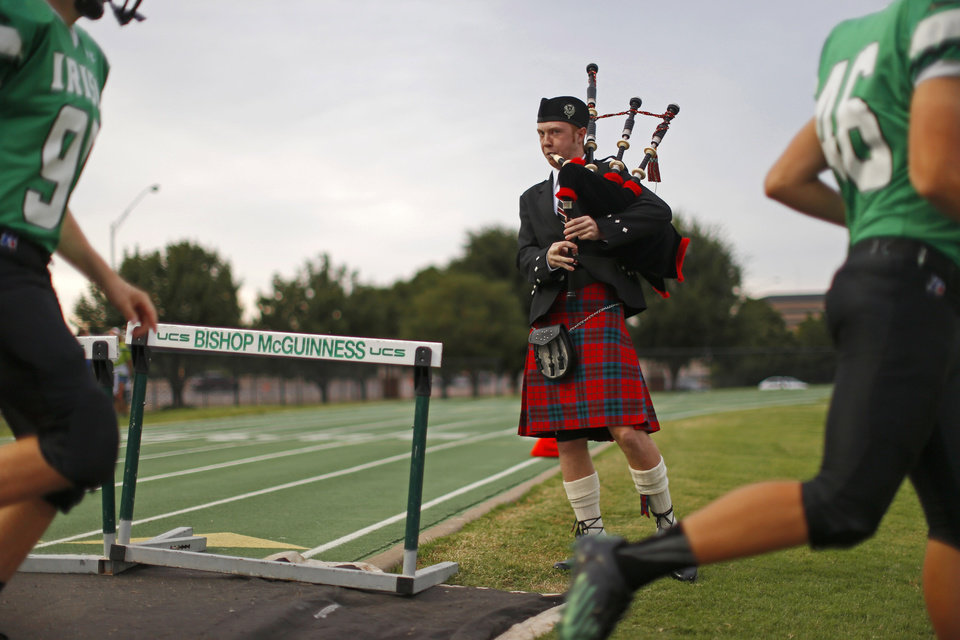 Photo - Bishop McGuinness junior Ian Smith, 17, plays bagpipes as the football team walks onto the field prior to their game against Weatherford in Oklahoma City, Friday, Sept. 20, 2013. Photo by Bryan Terry, The Oklahoman