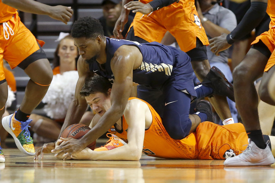 Photo - Oklahoma State's Hidde Roessink (35) dives for the ball under Oral Roberts' Emmanuel Nzekwesi (23) during an NCAA basketball game between the Oklahoma State University Cowboys (OSU) and the Oral Roberts Golden Eagles (ORU) at Gallagher-Iba Arena in Stillwater, Okla., Wednesday, Nov. 6, 2019. [Bryan Terry/The Oklahoman]