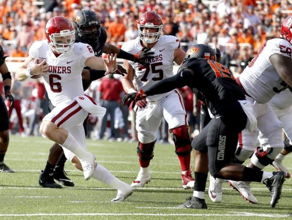 Photo -  Baker Mayfield had many iconic moments at OU, but this was his literal Heisman moment in the Sooners' 2017 Bedlam win as he prepared to stiff-arm Oklahoma State's Justin Phillips just as the trophy would. [Sarah Phipps/The Oklahoman]