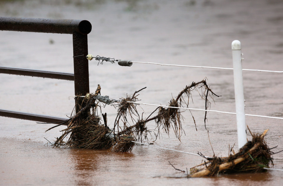 Photo - Debris is hung up in a fence along this road in Shawnee after rain from Hurricane Bill produced localized flooding in areas of Pottawatomie County on Thursday, June 18,  2015.   Hardesty Road and US 177. Photo by Jim Beckel, The Oklahoman.