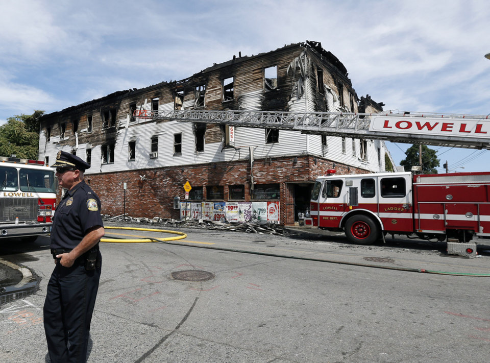 Photo - A policeman secures the scene of a burned three-story apartment and business building in Lowell, Mass., Thursday, July 10, 2014, where officials said seven people died in a fast-moving pre-dawn fire.  A police officer on routine patrol was the first to report the fire just before 4 a.m., while several tenants ran about 100 yards down the street to the nearest fire station to sound the alarm, Fire Chief Edward Pitta said. (AP Photo/Elise Amendola)