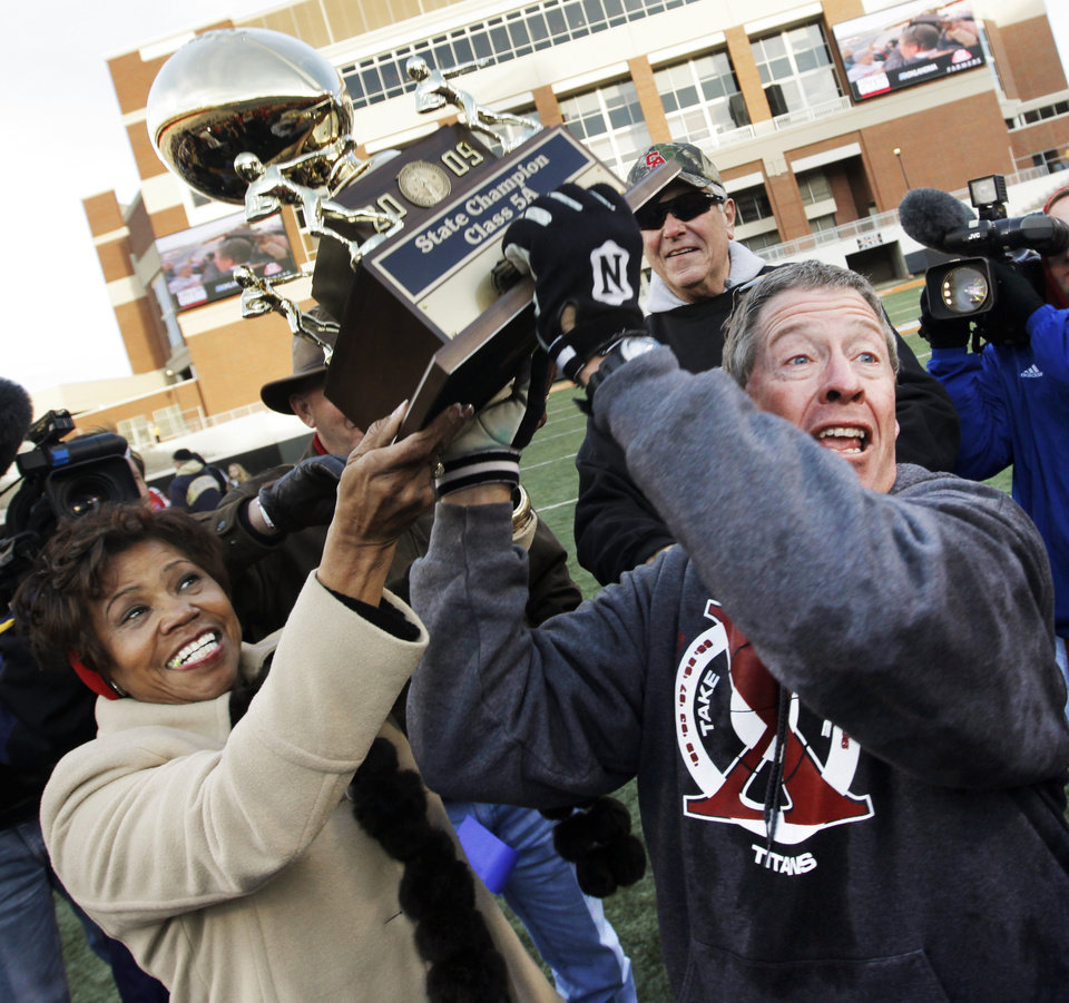 Photo - Carl Albert principal Dr. Silvya Kirk, left, and head coach Gary Rose bring the championship trophy to the Titans after the Class 5A state high school football championship game between Bixby and Carl Albert at Boone Pickens Stadium in Stillwater, Okla., Saturday, December 5, 2009. Carl Albert won, 21-7.  Photo by Nate Billings, The Oklahoman