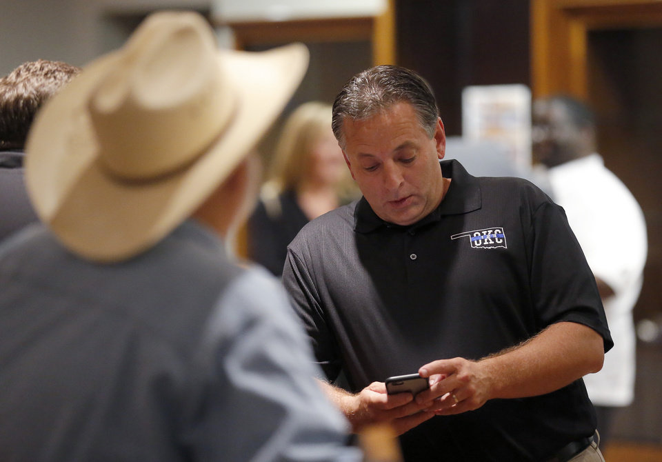 Photo -  John George, president of Oklahoma City Fraternal Order of Police Lodge 123, checks election results Tuesday at the FOP building in Oklahoma City. [Photo by Sarah Phipps, The Oklahoman]
