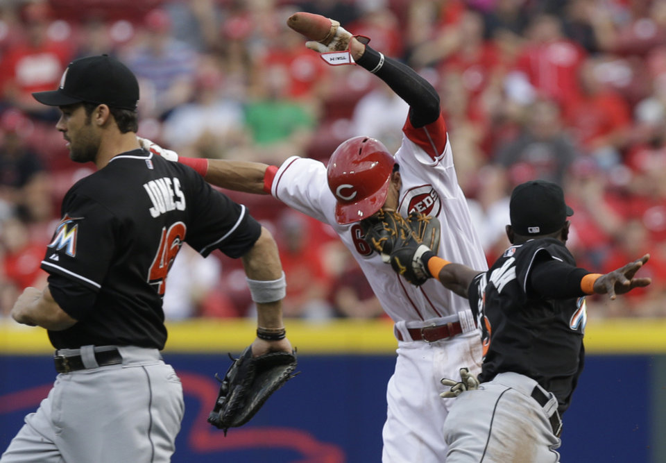 Photo - Cincinnati Reds' Billy Hamilton, center, is tagged out by Miami Marlins shortstop Adeiny Hechavarria, right, after getting caught in a rundown between first and second base in the first inning of a baseball game, Friday, Aug. 8, 2014, in Cincinnati. Marlins first baseman Garrett Jones, left, runs by. (AP Photo/Al Behrman)