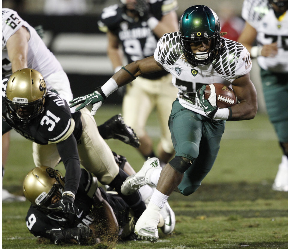 Photo - Oregon running back Ayele Forde, right, gets away from Colorado outside linebacker Kenneth Olugbode, top left, and defensive backer Tedric Thompson for a long gain in the fourth quarter of Oregon's 57-16 victory in an NCAA college football game in Boulder, Colo., on Saturday, Oct. 5, 2013. (AP Photo/David Zalubowski)