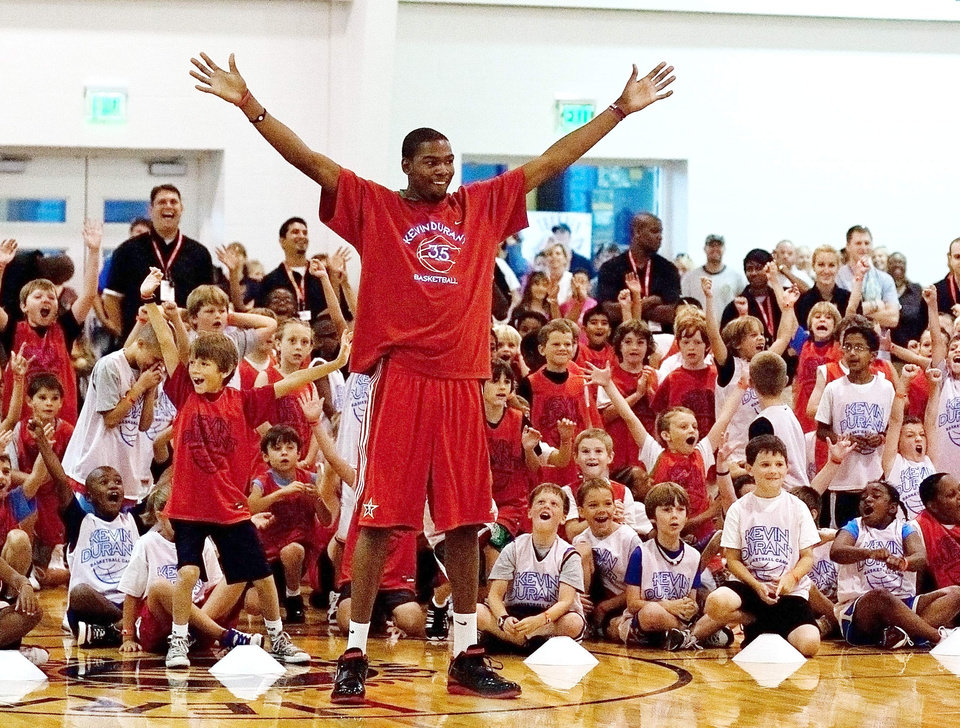Photo - Oklahoma City Thunder forward Kevin Durant reacts with kids after making a back-to-the-basket, half-court shot Wednesday, June 30, 2010, at a basketball camp at Heritage Hall in Oklahoma City. Mitchell Alcala, The Oklahoman.