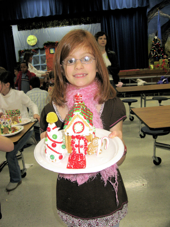 Chisholm Elementary third-grader Ali Boone proudly displays her freshly built gingerbread house.  Photo by Lillie-Beth Brinkman,  THE OKLAHOMAN