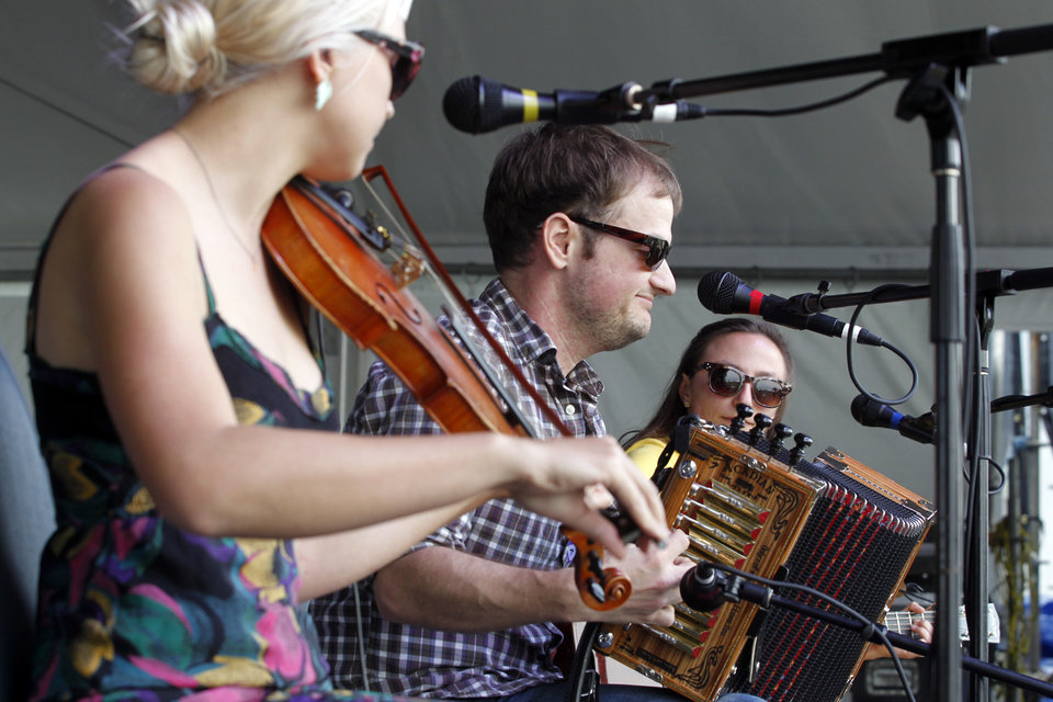 The Cajun band T'Monde performs on the Fais Do Do stage during the New Orleans Jazz and Heritage Festival in New Orleans, Friday, April 26, 2013. From left are band members Kelli Jones-Savoy playing fiddle, Drew Simon on the accordion, and Megan Brown on guitar. (AP Photo/Doug Parker)