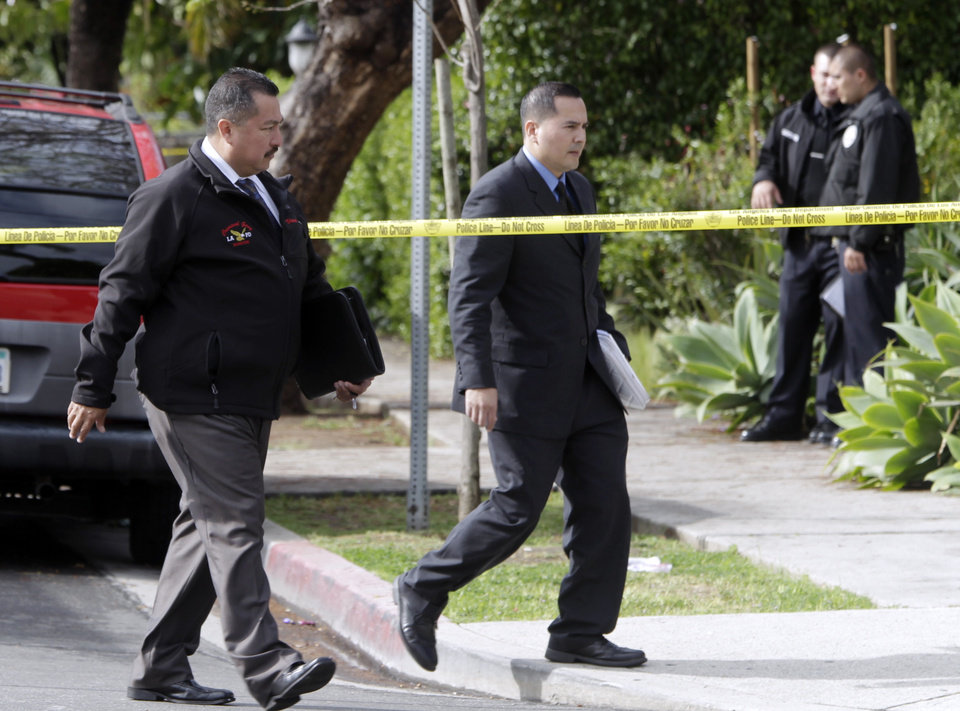 Photo -   Los Angeles Police Department investigators work at the scene of a shooting of two USC students in Los Angeles on Wednesday, April 11, 2012. Police said a gunman opened fire on a BMW near the University of Southern California campus on Wednesday, killing two international students from China in what may have been a bungled carjacking attempt. (AP Photo Damian Dovarganes)