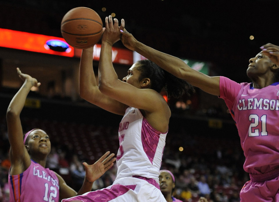 Photo - Maryland's Alyssa Thomas, center, is fouled by Clemson's Nikki Dixon, right, as Clemson's Quinyotta Pettaway defends at left, in the second half of an NCAA college basketball game on Sunday, Feb. 9, 2014, in College Park, Md. Maryland won 95-43. (AP Photo/Gail Burton)