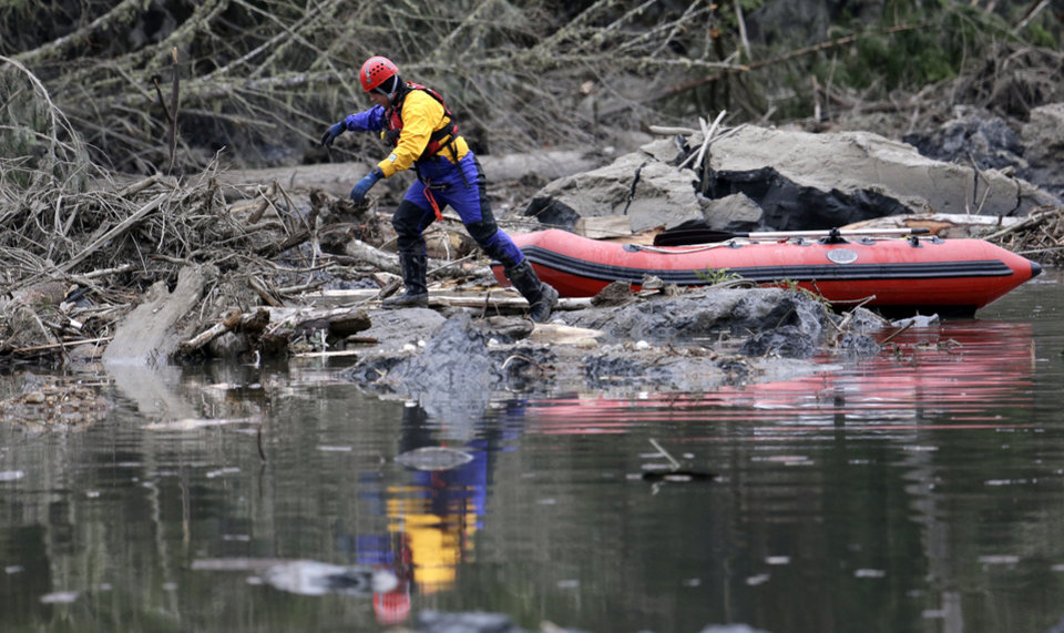 Photo - A searcher steps off of his boat to look through debris following a deadly mudslide, Tuesday, March 25, 2014, in Oso, Wash. At least 14 people were killed in the 1-square-mile slide that hit in a rural area about 55 miles northeast of Seattle on Saturday. Several people also were critically injured, and homes were destroyed. (AP Photo/Elaine Thompson)