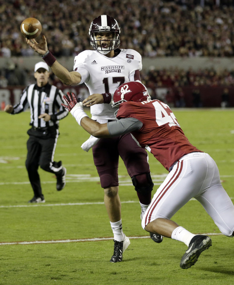 Photo -   Mississippi State quarterback Tyler Russell (17) throws despite the defense of Alabama linebacker Adrian Hubbard (42) during the first half of an NCAA college football game at Bryant-Denny Stadium in Tuscaloosa, Ala., Saturday, Oct. 27, 2012. (AP Photo/Dave Martin)