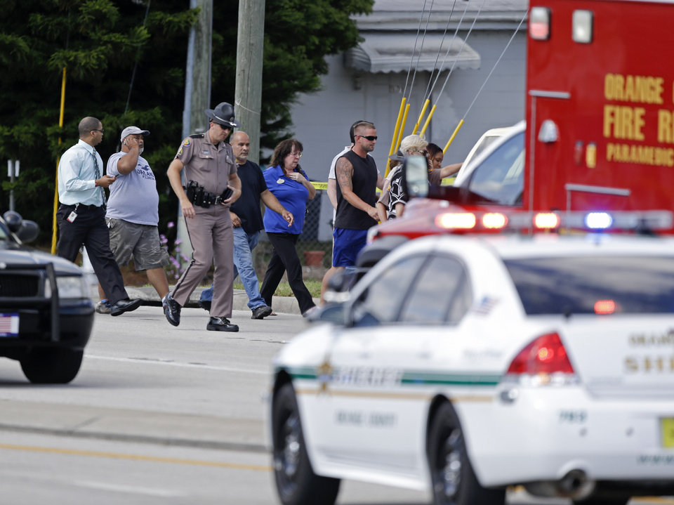 Photo - A Florida state trooper, center, escorts a group of parents to a day care center to pick up their children after a vehicle crashed into the center, Wednesday, April 9, 2014, in Winter Park, Fla. At least 15 people were injured, including children. (AP Photo/John Raoux)