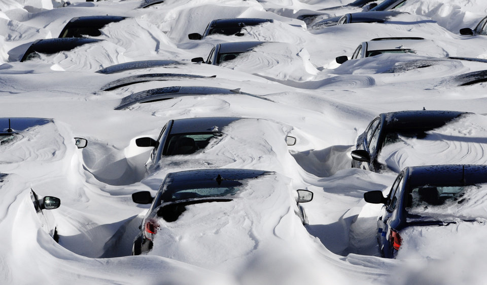 Photo - Snow begins to melt on cars parked at a dealership after a winter storm in Hartford, Conn., Sunday, Feb. 10, 2013.  A howling storm across the Northeast left much of the New York-to-Boston corridor covered with more than three feet of snow on Friday into Saturday morning. (AP Photo/Jessica Hill)