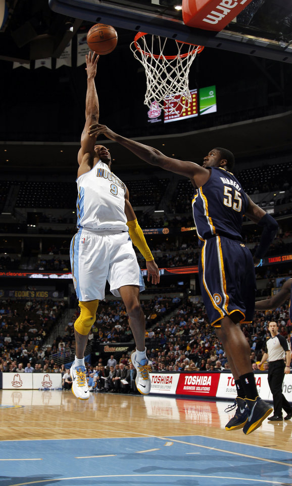 Denver Nuggets guard Andre Iguodala, left, drives the lane for a shot over Indiana Pacers center Roy Hibbert in the first quarter of an NBA basketball game in Denver on Monday, Jan. 28, 2013. (AP Photo/David Zalubowski)