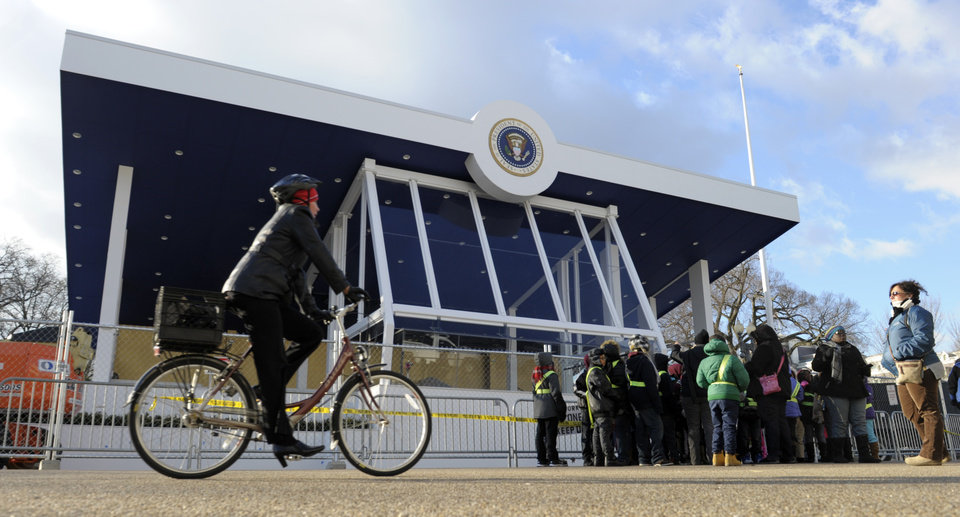 Photo - A cyclist prepares to pass visitors standing in front of the Inaugural Parade Reviewing Stand outside the White House on Pennsylvania Avenue in Washington, Friday, Jan. 18, 2013, in preparation for this weekend's 57th Presidential Inauguration