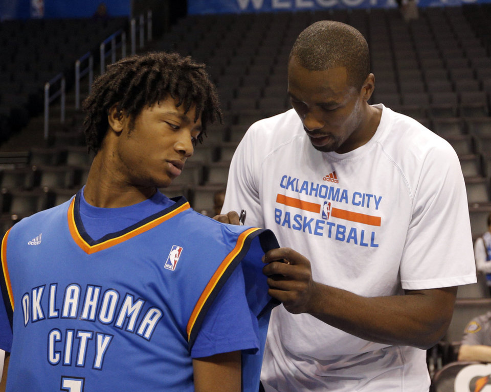 Photo - Serge Ibaka (9) signs a jersey for Warren Lewis as part of his Make-a-Wish before the NBA game between the Oklahoma City Thunder and the Utah Jazz at the Chesapeake Energy Arena, Sunday, March 30, 2014, in Oklahoma City. Photo by Sarah Phipps, The Oklahoman