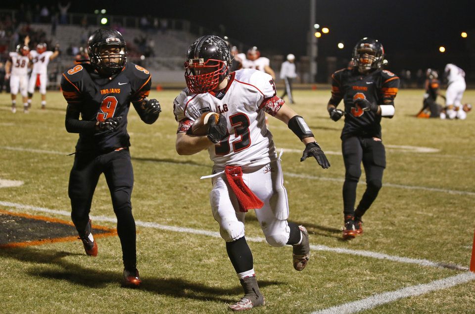Photo - Locust Grove's Vance Wilson scores a touchdown in front of Douglass' Terrance Bagby, left, and Sergio Nelson during their high school football playoff game at Douglass in Oklahoma City, Friday, Nov. 28, 2014. Photo by Bryan Terry, The Oklahoman