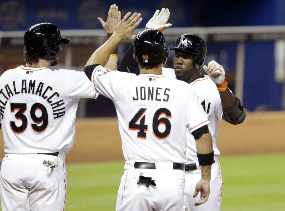 Photo - Miami Marlins' Marcell Ozuna, right, is met by teammates Jarrod Saltalamacchia (39) and Garrett Jones (46) after scoring on a three-run home run during the second inning of a baseball gam against the Atlanta Braves, Wednesday, April 30, 2014, in Miami. (AP Photo)