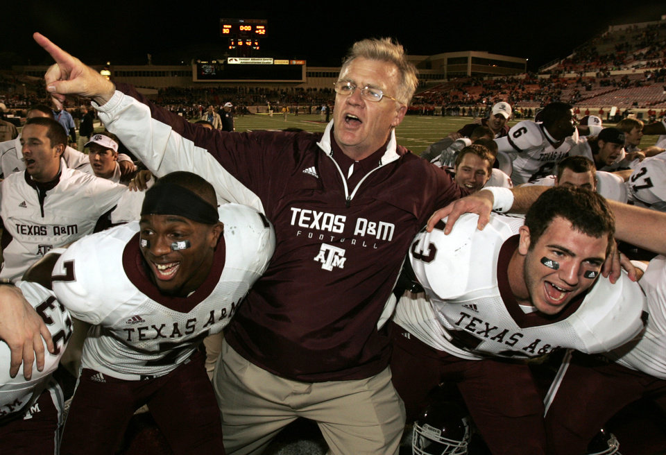 Photo - CELEBRATION: Texas A&M University head coach Mike Sherman celebrates with players Uzoma Nwachukwu (7) and Aaron Arterburn (43) and the rest of the team after an NCAA college football game against Texas Tech University in Lubbock, Texas, Saturday, Oct. 24, 2009. Texas A&M won 52 - 30. (AP Photo/Mike Fuentes) ORG XMIT: TXMF111
