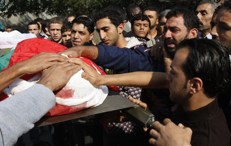 Photo -   Palestinians carry the body of Osama Shehada, 17, during his funeral in the Nuseirat Refugee Camp, central Gaza Strip, Tuesday, Nov. 20, 2012. Shehada was killed in an Israeli air strike on Monday while walking with his uncle in the camp, neighbors said. (AP Photo/Adel Hana)
