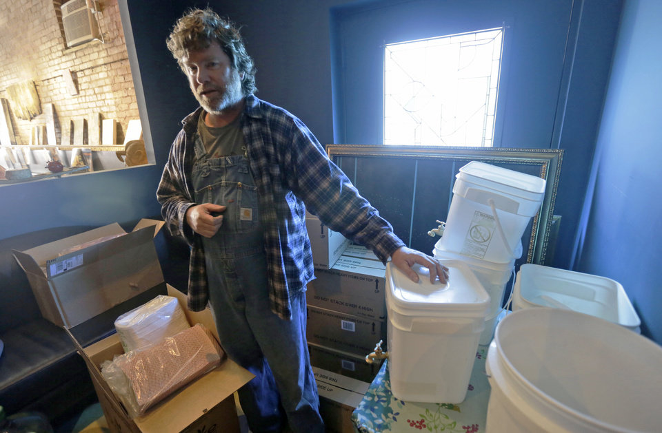Photo - Jonathan Steele, owner of Bluegrass Kitchen, displays hand washing stations that he used in the back of his restaurant in Charleston, W.Va., Tuesday, Jan. 14, 2014. Steele was able to open his restaurant using bottled water on Sunday.  He is still using bottled water to cook with.  (AP Photo/Steve Helber)