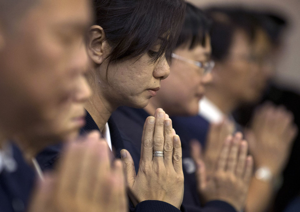 Photo - Volunteers from Taiwan's Buddhist association offer prayers for the Chinese passengers aboard the missing Malaysia Airlines flight MH370, at a hotel in Beijing, China Tuesday, April 1, 2014. Although it has been slow, difficult and frustrating so far, the search for the missing Malaysia Airlines jet is nowhere near the point of being scaled back, Australia's Prime Minister Tony Abbott said. The three-week hunt for Flight 370 has turned up no sign of the Boeing 777, which vanished March 8 with 239 people bound for Beijing from Kuala Lumpur. (AP Photo/Andy Wong)
