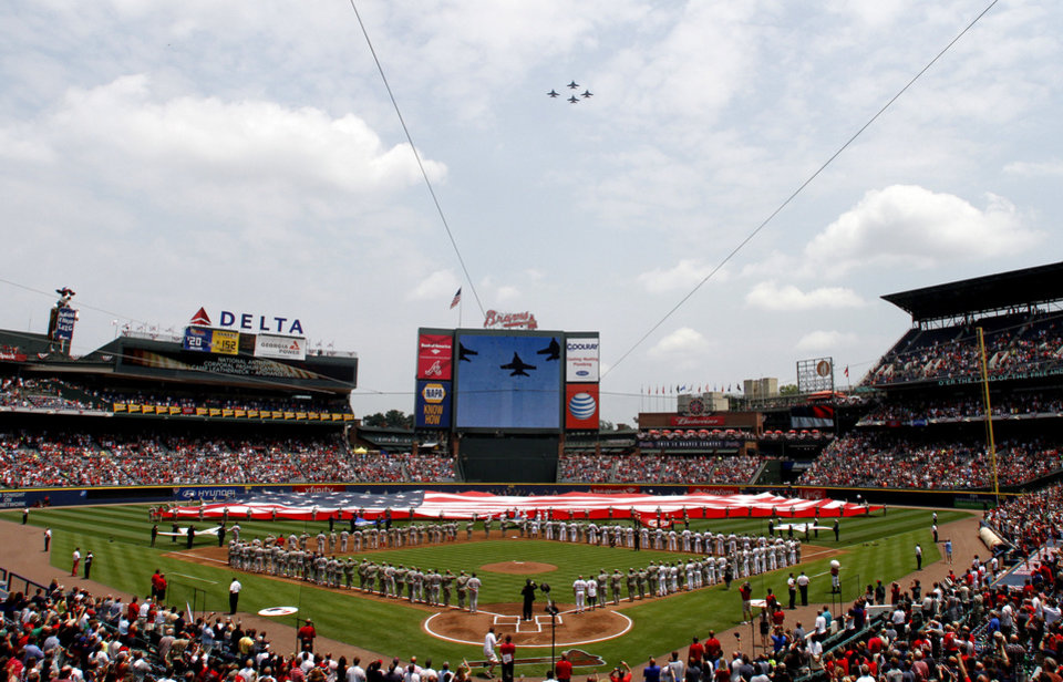 Photo - Jets fly over as members of the U.S. Military hold the American Flag across the outfield, in honor of Memorial Day, before a baseball game between the Atlanta Braves and the Boston Red Sox on Monday, May 26, 2014, in Atlanta, Ga. (AP Photo/Butch Dill)