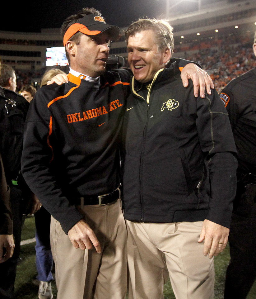 Photo - OSU coach Mike Gundy and Colorado coach Dan Hawkins talk after the college football game between Oklahoma State University (OSU) and the University of Colorado (CU) at Boone Pickens Stadium in Stillwater, Okla., Thursday, Nov. 19, 2009. Photo by Bryan Terry, The Oklahoman