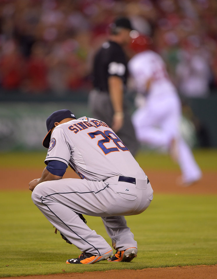 Photo - Houston Astros first baseman Jon Singleton, below, squats down as Los Angeles Angels' C.J. Cron round second after hitting a three-run home run during the seventh inning of a baseball game, Saturday, July 5, 2014, in, Anaheim, Calif.  (AP Photo/Mark J. Terrill)