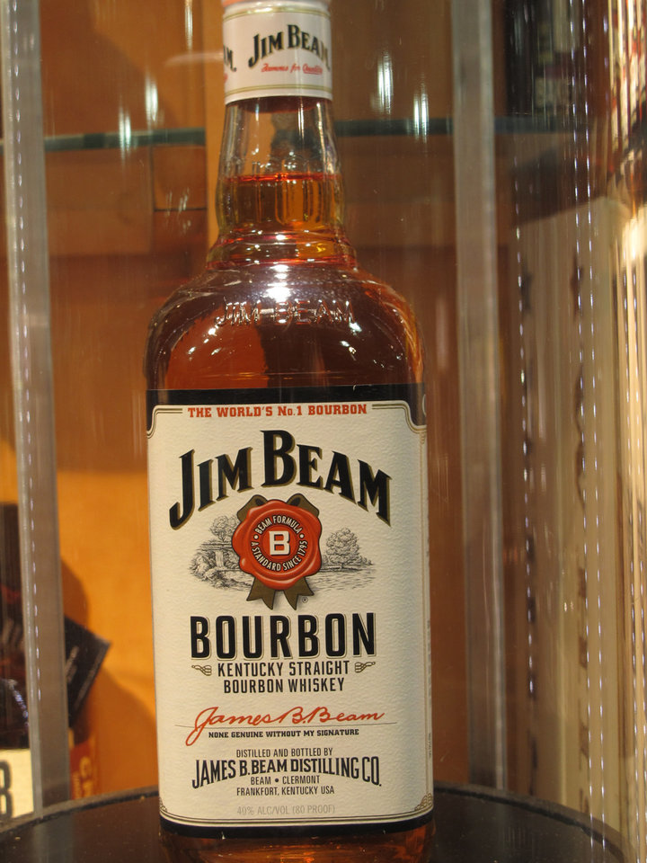 Photo - In this Monday, Jan. 13, 2014, photo, a Jim Beam bourbon bottle is on display at the Jim Beam visitors' center at Clermont, Ky. The bourbon brands will be acquired by Japanese-based Suntory Holdings Ltd. as part of its planned $13.6 billion acquisition of Beam Inc. Whiskey insiders say Kentucky bourbon still ranks as authentically American, even when some of its distillers answer to foreign companies. (AP Photo/Bruce Schreiner)
