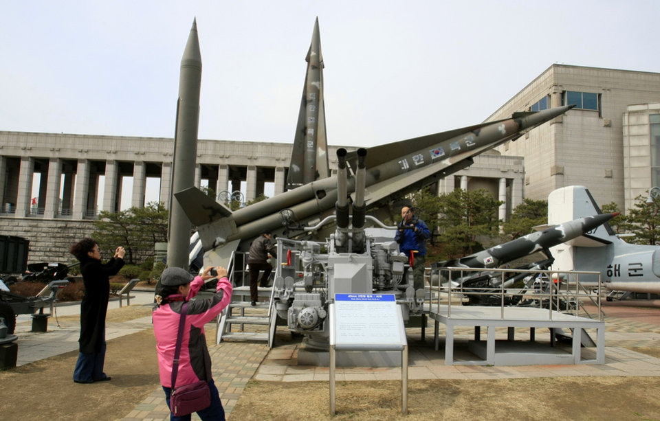 Photo -   Foreign visitors take souvenir photos near a mock North Korean Scud-B missile, back left, and other South Korean missiles at the Korea War Memorial Museum in Seoul, Monday, March 19, 2012. North Korea vowed Sunday to go ahead with plans to launch a long-range rocket, rejecting criticism in the West that it would scuttle recent diplomacy. (AP Photo/Lee Jin-man)