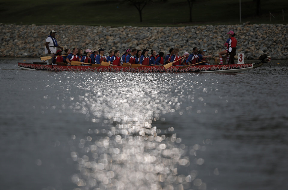 Photo - A dragon boat paddles down the Oklahoma River during the Oklahoma Regatta Festival Night Sprints in Oklahoma City, Thursday, Sept. 27, 2012.  Photo by Garett Fisbeck, The Oklahoman