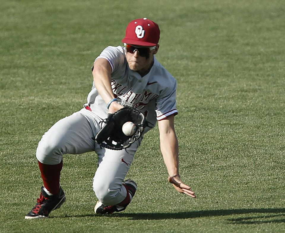 Photo - Oklahoma's Craig Aikin (3) makes a catch in the outfield during the bedlam matchup between the University of Oklahoma and Oklahoma State University in the Phillips 66 Big 12 Baseball Championship in Oklahoma City, Okla. on Wednesday, May 21, 2014.   Photo by Chris Landsberger, The Oklahoman