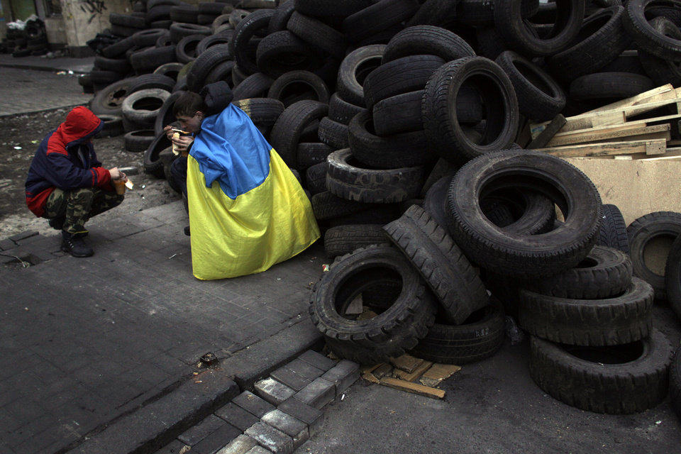 Photo - Anti-Yanukovych protesters eat next to a barricade at Kiev's Independence Square, the epicenter of the country's current unrest, Ukraine,  Thursday, Feb. 27, 2014. Ukraine put its police on high alert after dozens of armed pro-Russia men stormed and seized local government buildings in Ukraine's Crimea region early Thursday and raised a Russian flag over a barricade. (AP Photo/Marko Drobnjakovic)